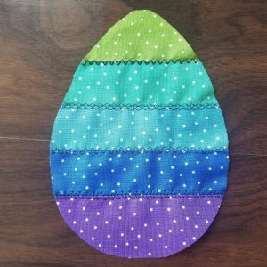 colorful sewn easter egg using strips of fabric and decorative sewing machine stitches