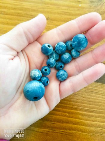 blue colorwashed beads in a hand