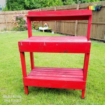 red potting bench in backyard
