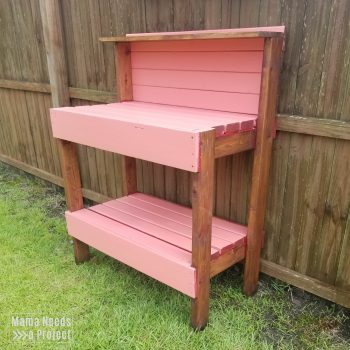 pink and dark wood garden potting bench against fence