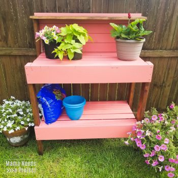 pink garden potting bench with flowers
