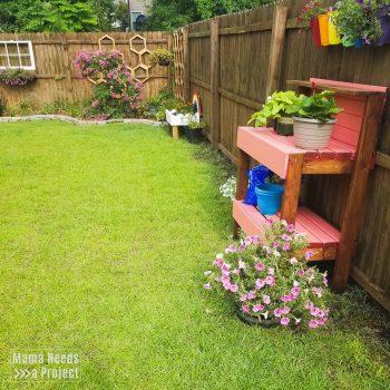 backyard garden with window box, trellis, potting bench, many flowers