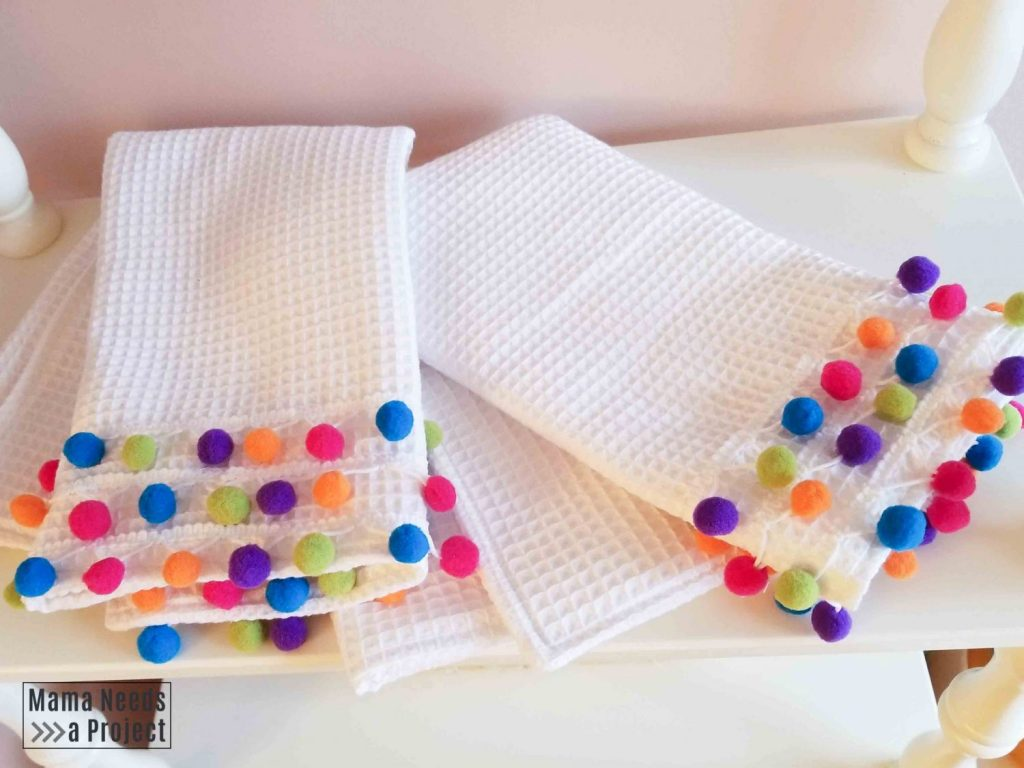 2 diy pom pom towels on a white shelf