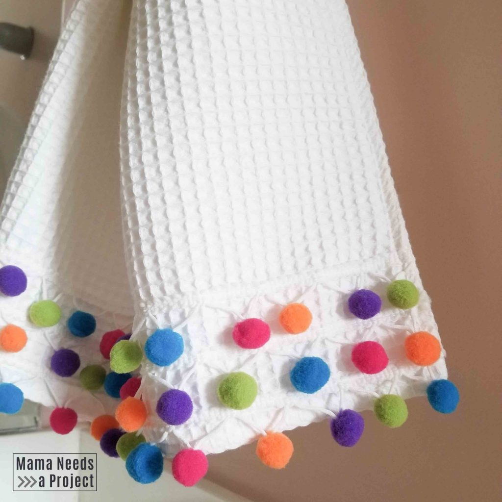 white pom pom towel hanging in bathroom