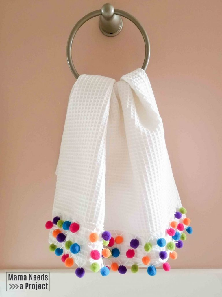 colorful diy pom pom towel hanging against a pink wall
