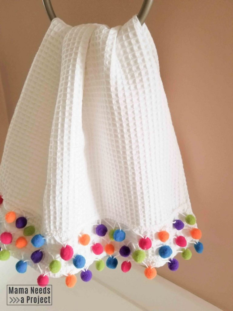 diy pom pom towel with rainbow pom poms in a pink bathroom