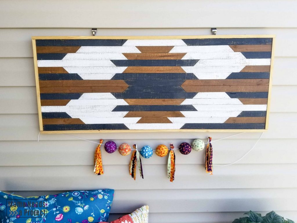 diy geometric wall art, outdoor wall art with a colorful garland underneath