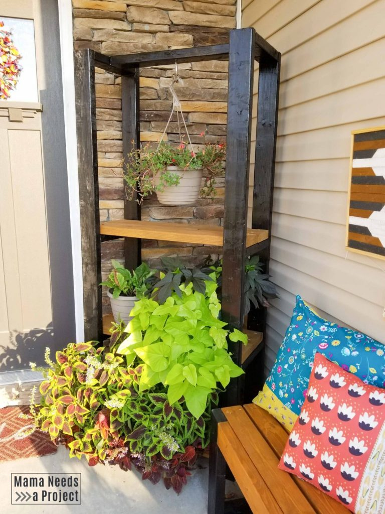 diy outdoor plant shelf on front porch with many plants and other diy front porch decor