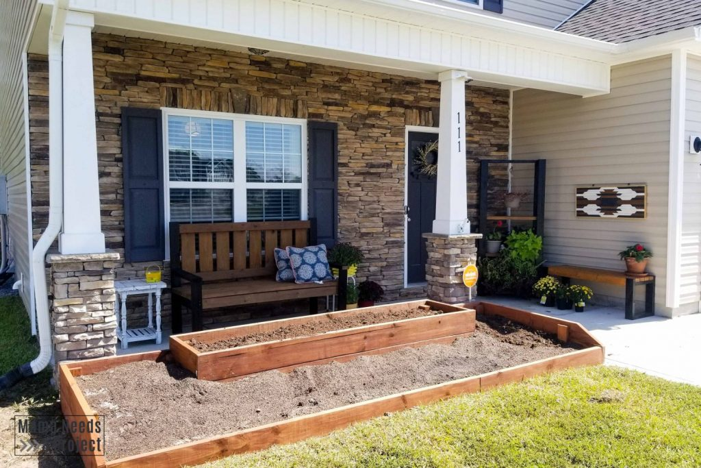 front porch with raised flower bed, benches, wall art, flowers, plant shelf