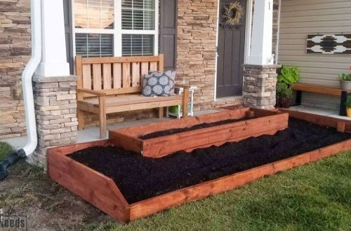 wood raised flower bed on front of home