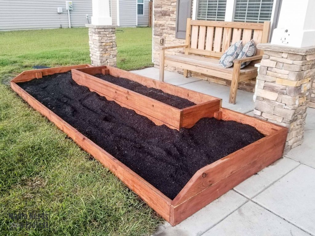 wood raised flower bed in front of home