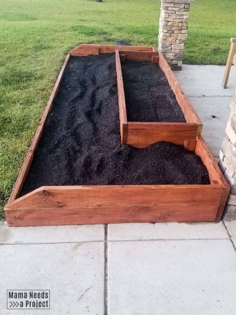 wood raised flower bed in front of home, stained dark reddish brown with dark soil
