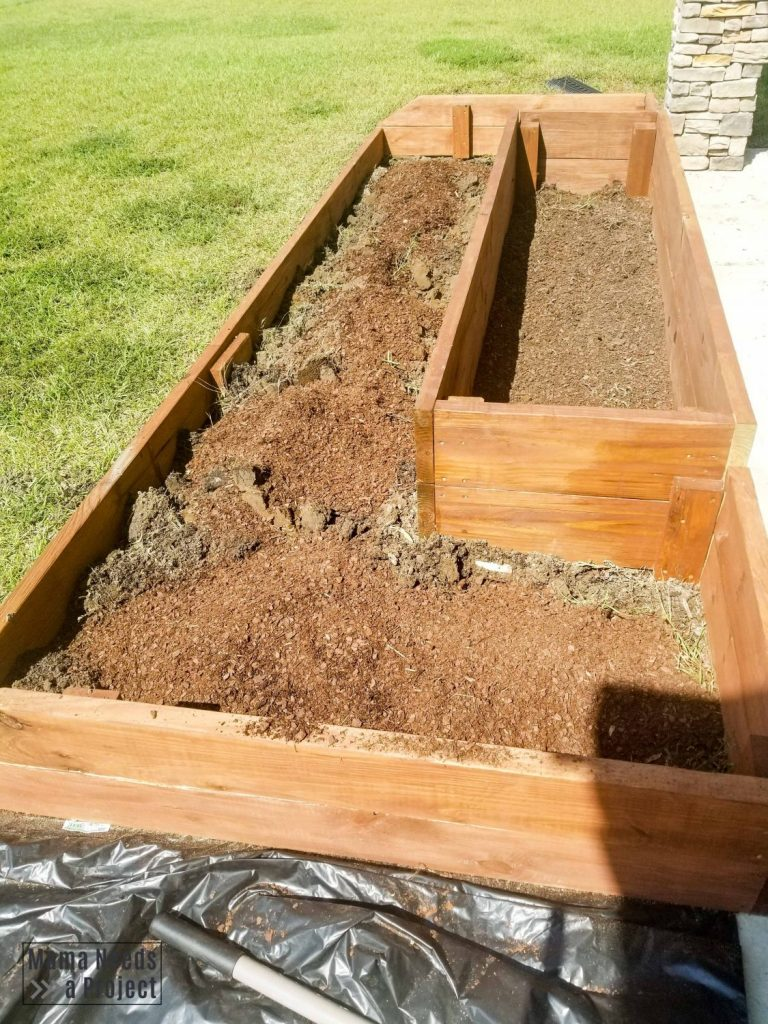 soil conditioner on top of clay soil in raised flower bed