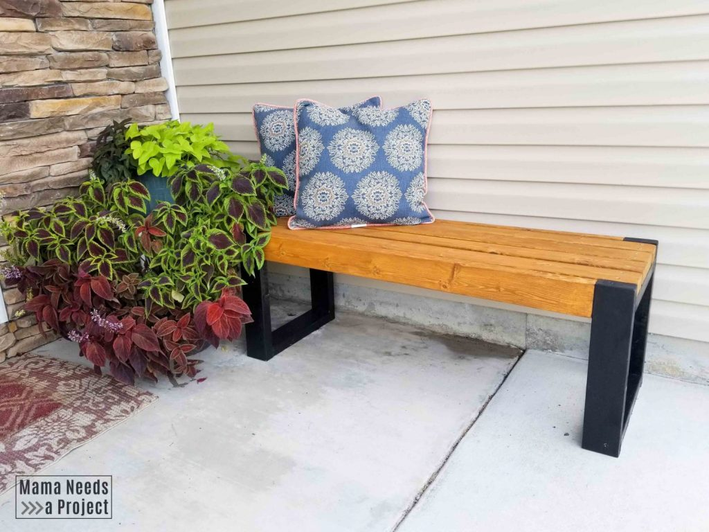 two tone simple 2x4 bench on front porch with pillows and plants