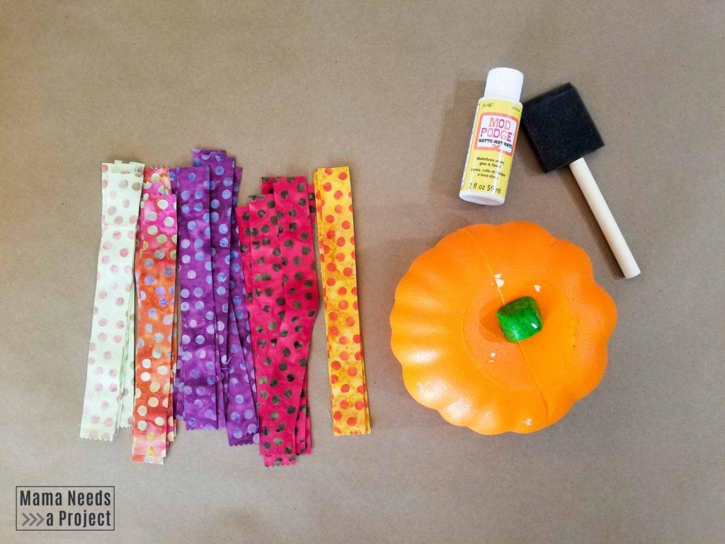 scrap fabric pumpkin supplies - foam brush, mod podge, foam pumpkin, scrap fabric strips