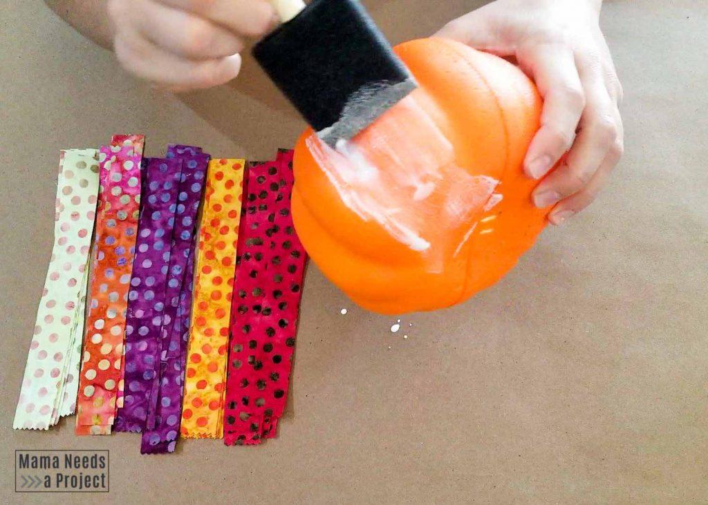 apply mod podge to foam pumpkin