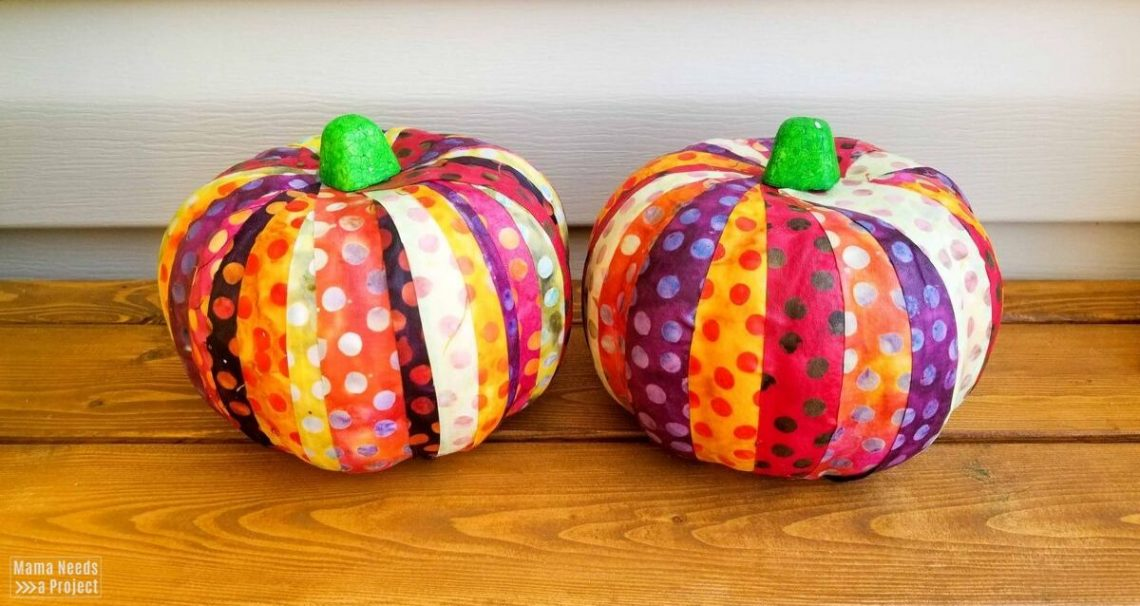 two colorful scrap fabric pumpkins on a wood bench