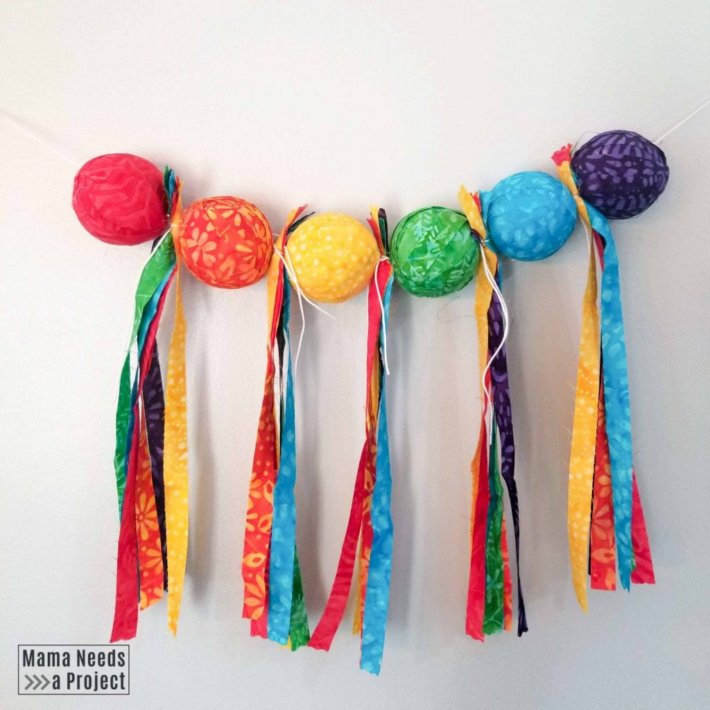 rainbow scrap fabric garland with fabric covered foam balls and fabric tassels