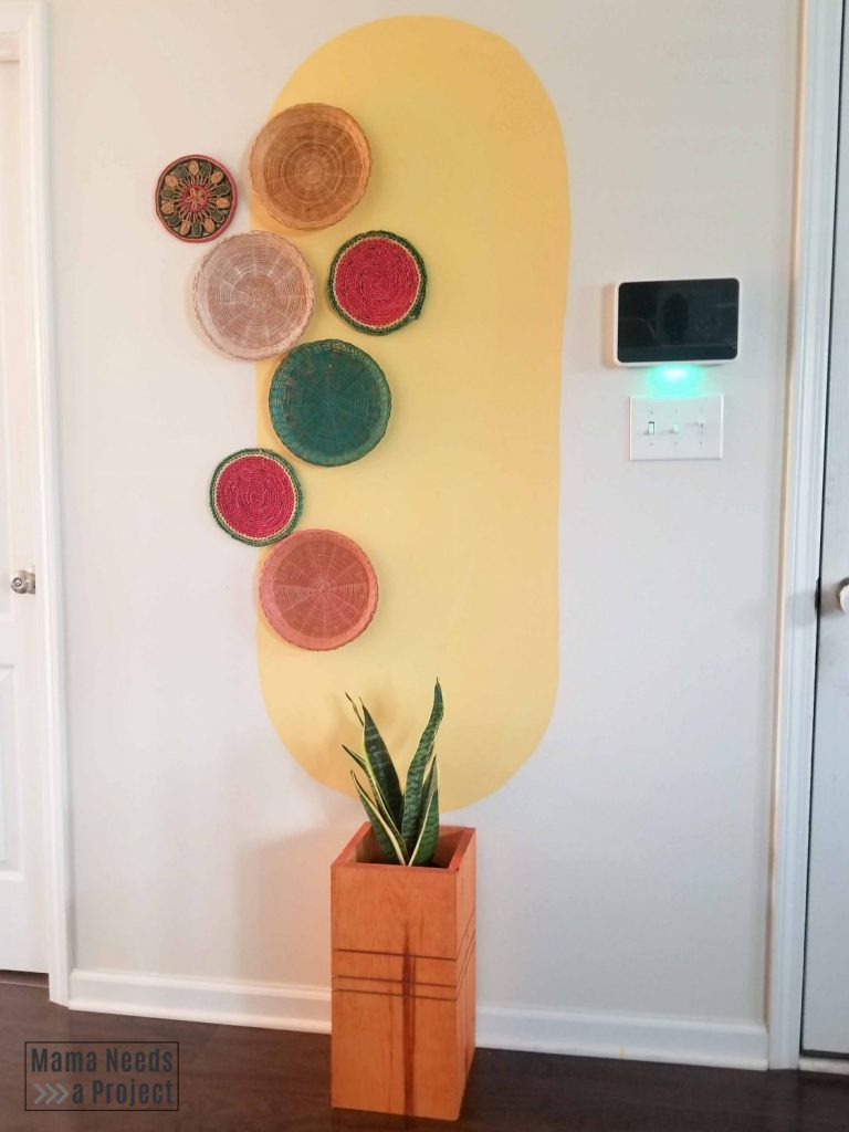 large yellow oval painted on wall with colored baskets and wood planter