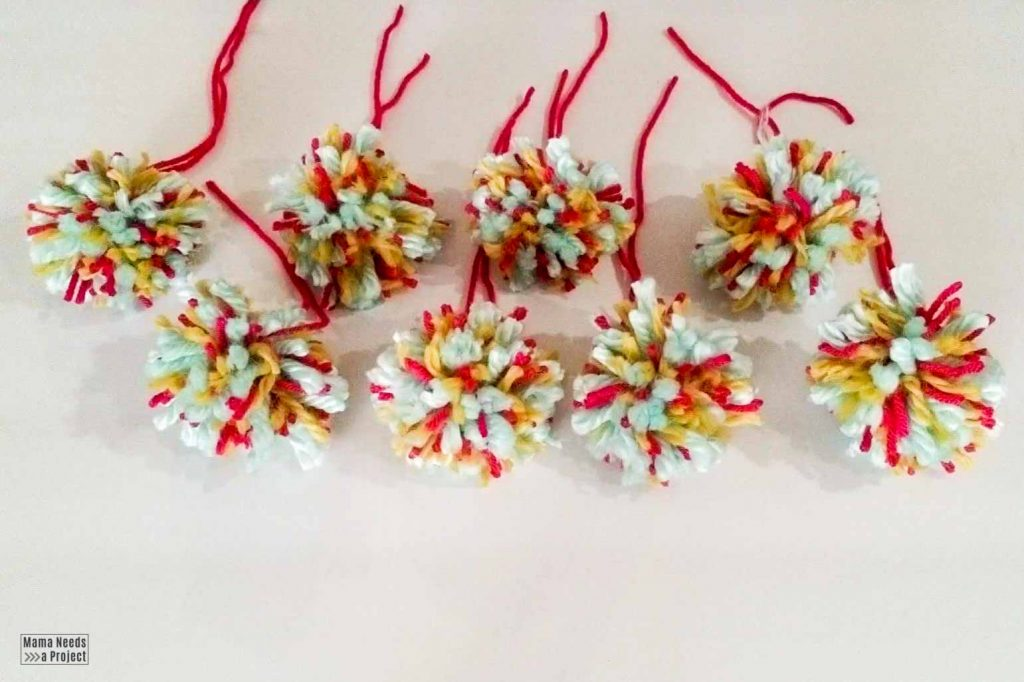 8 completed speckled pom poms for pom pom wreath