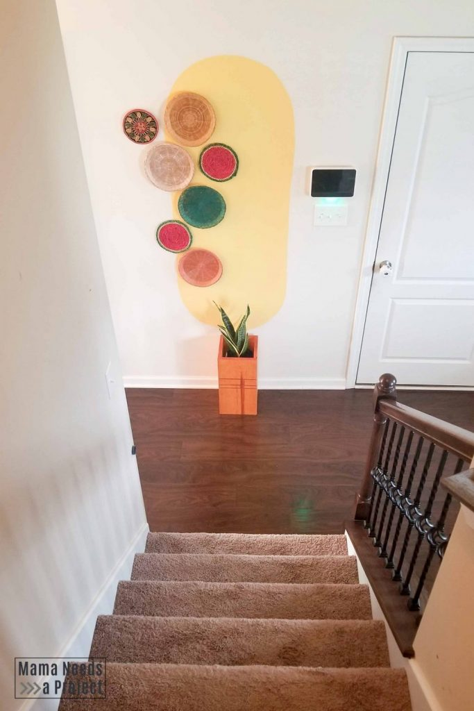 large yellow oval at the bottom of a staircase with colorful baskets and plant