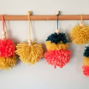 pom pom christmas ornaments hanging from a wooden dowel