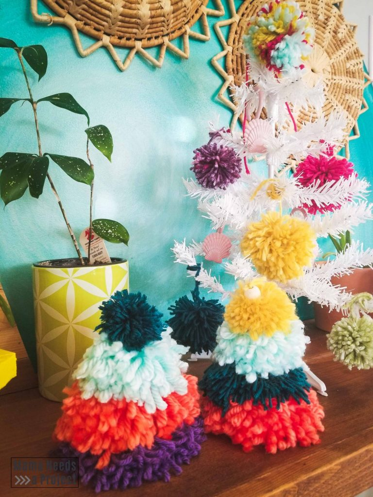 two pom pom christmas trees in front of watercolor inspired teal wall