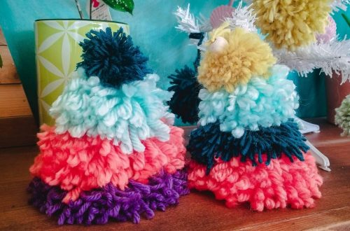 two colorful pom pom christmas trees in front front of a teal wall