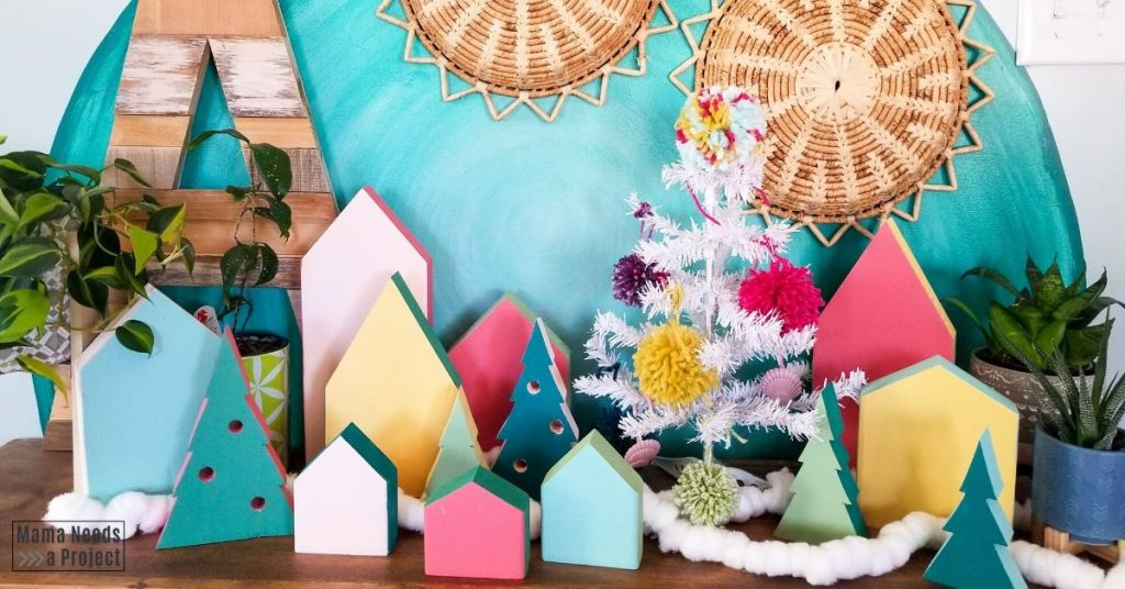 scrap wood christmas village against a teal wall with holiday decor