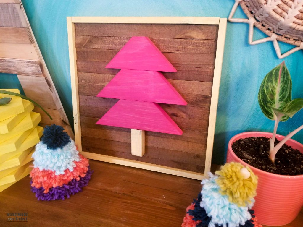 pink scrap wood christmas tree on a blue wall with colorful christmas decor