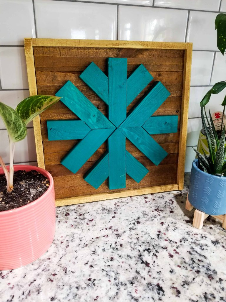 teal scrap wood framed snowflake on a kitchen counter with plants