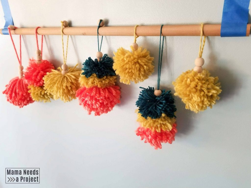 pom pom christmas ornaments hanging on a rod