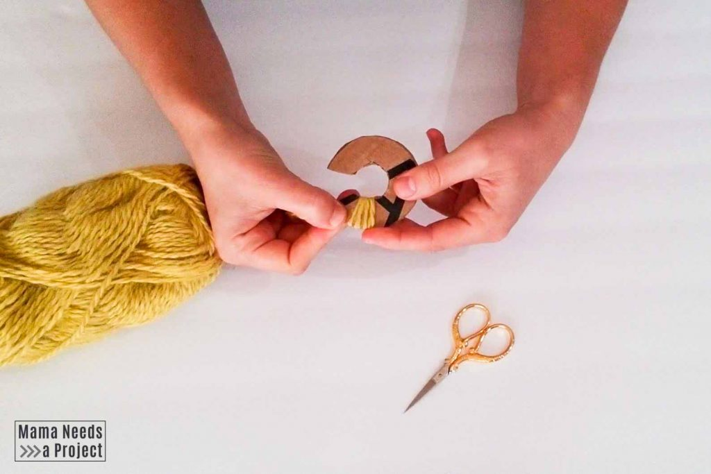 wrap yarn around pom pom maker