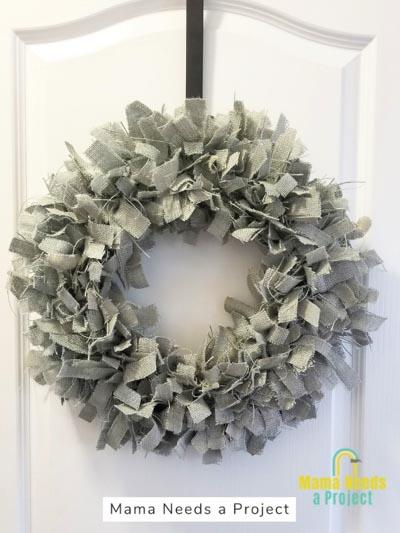 light blue burlap rag wreath hanging on a white door