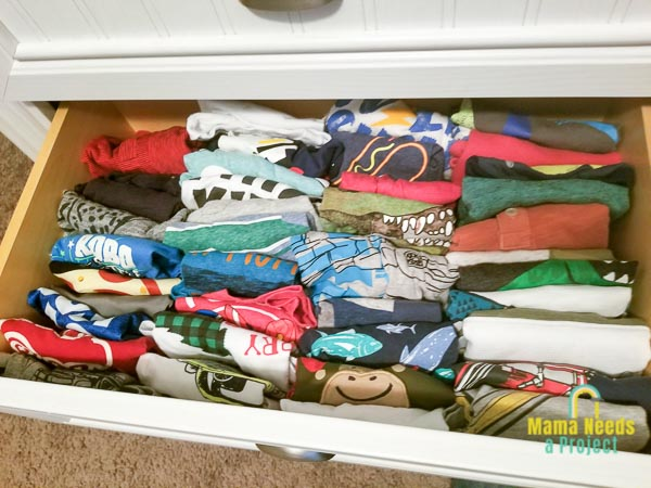 baby clothes folded konmari style in a dresser drawer