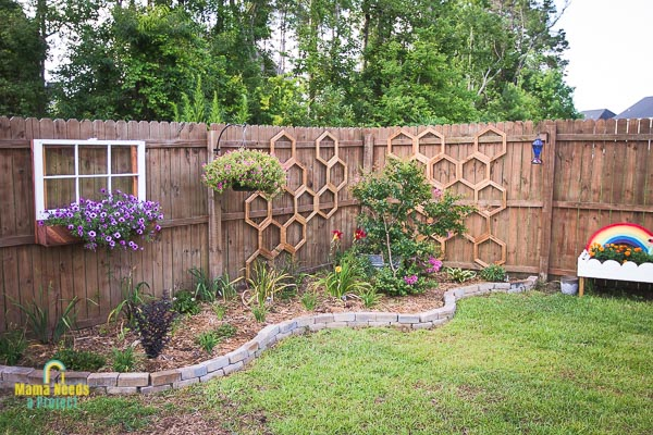 corner garden with diy garden trellis in a honeycomb shape, diy rainbow flower bed and fence mounted window and flower box