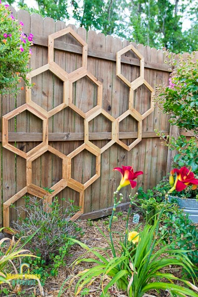 honeycomb diy garden trellis mounted onto fence with red flowers in front