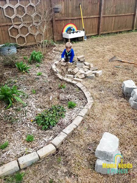 removing stone border to prepare flower garden for spring