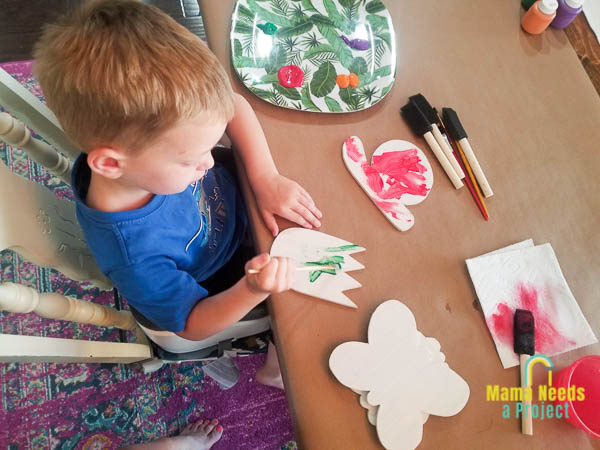 child painting diy garden signs cut from scrap plywood