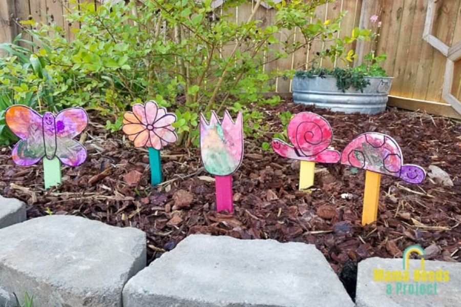 scrap wood garden signs painted by a child on display in a garden
