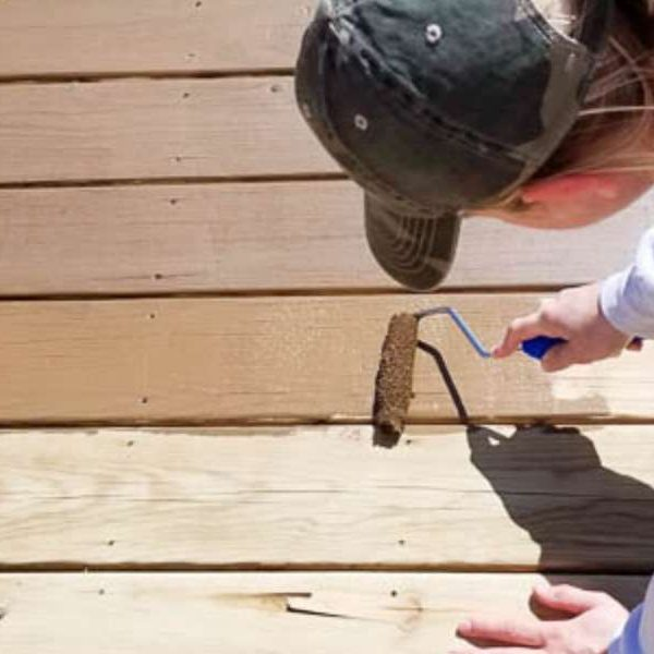 restaining a wood deck - woman staining wood deck with a roller