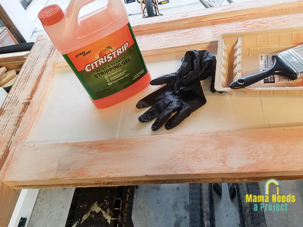 Jug of Citistrip, gloves, paint brush and plastic paint container on top of white twin headboard