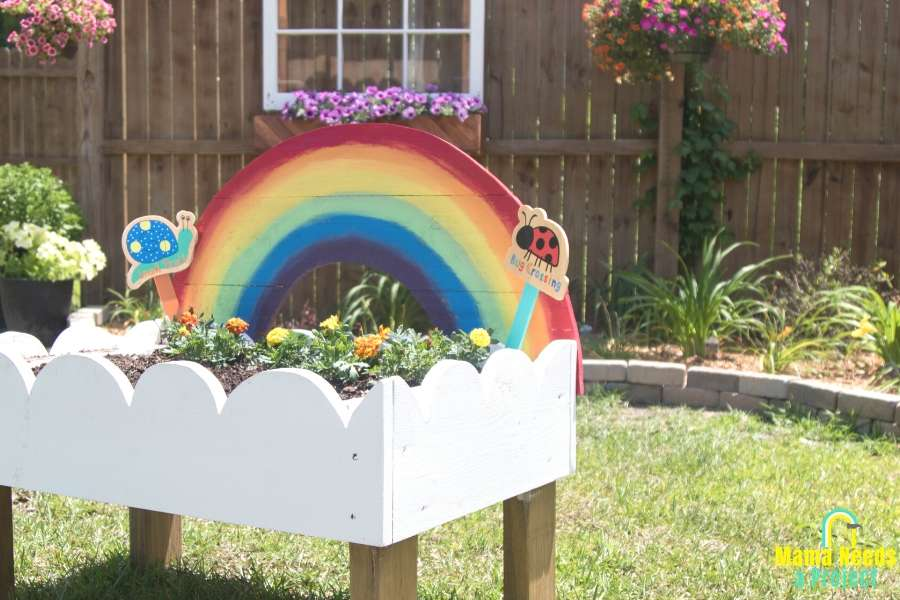 rainbow toddler garden in front of fence with window and flower box, hanging colorful flowers
