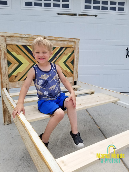 boy sitting on diy twin bed frame with geometric headboard