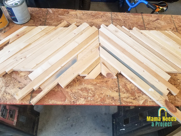 strips of wood on piece of plywood in a geometric design for diy twin bed frame foot board geometric insert