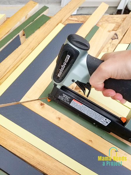 nail gun nailing down strips of painted wood onto plywood to create geometric design for twin bed frame