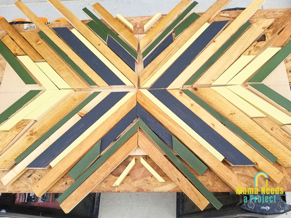 painted strips of wood on a piece of plywood in a geometric design