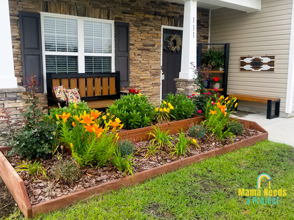 diy raised flower bed in front of home with several pieces of diy outdoor furniture and decor