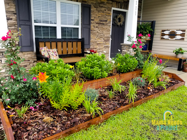 raised flower bed in front of house with many blooming flowers