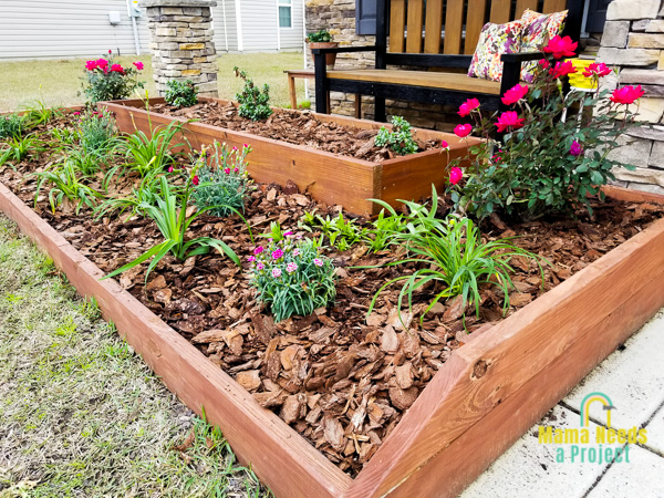 diy raised flower bed with newly planted flowers and mulch